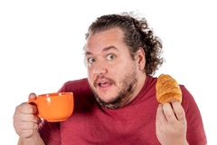 Funny fat man eating small croissant and drinking coffee from big orange cup on white background. Good morning and breakfast royalty free stock photo