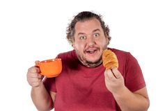 Funny fat man eating small croissant and drinking coffee from big orange cup on white background. Good morning and breakfast royalty free stock images