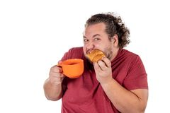 Funny fat man eating small croissant and drinking coffee from big orange cup on white background. Good morning and breakfast royalty free stock image