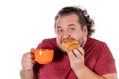 Funny fat man eating small croissant and drinking coffee from big orange cup on white background. Good morning and breakfast royalty free stock photos
