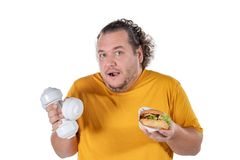 Funny fat man eating unhealthy food and trying to take exercise isolated on white background. Funny fat man eating unhealthy food and trying to take exercise royalty free stock photography