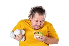 Funny fat man eating unhealthy food and trying to take exercise isolated on white background. Funny fat man eating unhealthy food and trying to take exercise stock images