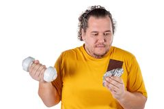 Funny fat man eating unhealthy food and trying to take exercise isolated on white background. Funny fat man eating unhealthy food and trying to take exercise stock photography