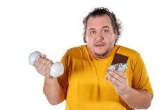 Funny fat man eating unhealthy food and trying to take exercise isolated on white background. Funny fat man eating unhealthy food and trying to take exercise royalty free stock photo