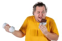 Funny fat man eating unhealthy food and trying to take exercise isolated on white background. Funny fat man eating unhealthy food and trying to take exercise royalty free stock images