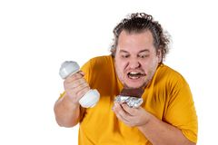 Funny fat man eating unhealthy food and trying to take exercise isolated on white background. Funny fat man eating unhealthy food and trying to take exercise stock photo