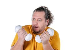 Funny fat man exercising with dumbbells and looking at camera isolated on white background. Funny fat man exercising with dumbbells and looking at camera royalty free stock photo