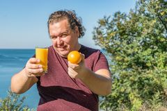Funny fat man on the ocean drinking juice and eating fruits. Vacation, weight loss and healthy eating stock photography