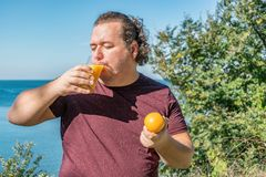 Funny fat man on the ocean drinking juice and eating fruits. Vacation, weight loss and healthy eating stock photos