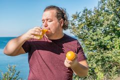 Funny fat man on the ocean drinking juice and eating fruits. Vacation, weight loss and healthy eating stock images