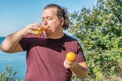 Funny fat man on the ocean drinking juice and eating fruits. Vacation, weight loss and healthy eating royalty free stock photos