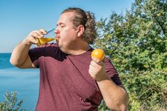 Funny fat man on the ocean drinking juice and eating fruits. Vacation, weight loss and healthy eating royalty free stock photo