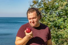 Funny fat man on the ocean eating fruits. Vacation, weight loss and healthy eating royalty free stock photo