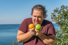 Funny fat man on the ocean eating fruits. Vacation, weight loss and healthy eating stock photos