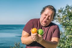 Funny fat man on the ocean eating fruits. Vacation, weight loss and healthy eating stock images
