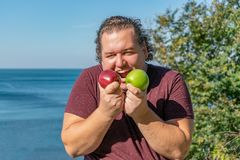 Funny fat man on the ocean eating fruits. Vacation, weight loss and healthy eating royalty free stock photography