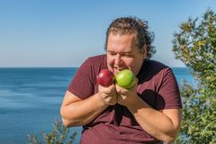 Funny fat man on the ocean eating fruits. Vacation, weight loss and healthy eating stock image