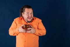 Funny fat man in orange shirt opens a box with a gift stock photography