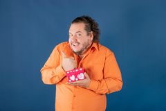 Funny fat man in orange shirt opens a box with a gift royalty free stock photography