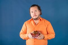 Funny fat man in orange shirt opens a box with a gift royalty free stock image