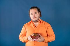 Funny fat man in orange shirt opens a box with a gift royalty free stock photos