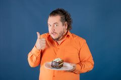Funny fat man in orange shirt with a piece of chocolate cake on a plate stock photo
