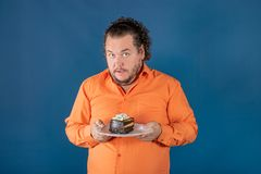 Funny fat man in orange shirt with a piece of chocolate cake on a plate stock image