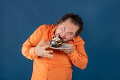Funny fat man in orange shirt with a piece of chocolate cake on a plate stock photos