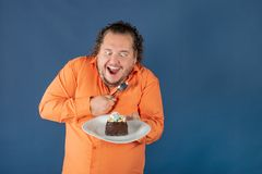 Funny fat man in orange shirt with a piece of chocolate cake on a plate stock images