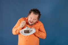 Funny fat man in orange shirt with a piece of chocolate cake on a plate royalty free stock image