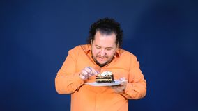 Funny fat man in orange shirt with a piece of chocolate cake on a plate. Birthday celebration stock video footage