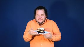 Funny fat man in orange shirt with a piece of chocolate cake on a plate. Birthday celebration stock video