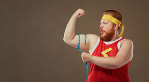 A funny fat man in sports clothes measures his arm with a centim royalty free stock photo