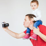 Funny father and child making selfie at vintage camera Stock Image