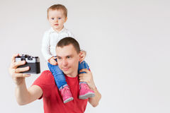Funny father and child making selfie at vintage camera Stock Images