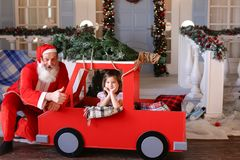 Funny Father Christmas doing thumbs up near gladden little princ royalty free stock photo