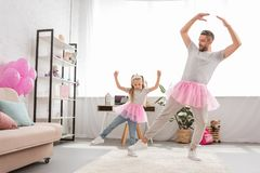 funny father and daughter in pink tutu skirts dancing stock photo