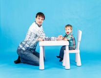 Funny father and little son competing in arm wrestling on blue. Background Stock Photo