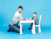 Funny father and little son competing in arm wrestling on blue. Background Royalty Free Stock Image