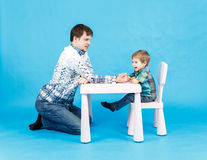 Funny father and little son competing in arm wrestling on blue Royalty Free Stock Photography