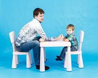 Funny father and little son competing in arm wrestling on blue Royalty Free Stock Photos