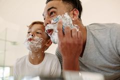 Funny father and son shaving in bathroom. Father and son  making funny faces while shaving in bathroom. Young men and little boy with shaving foam on their faces Royalty Free Stock Photography