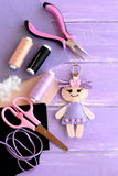 Funny felt doll keychain. Sewing supplies for toys. DIY kids embroidery inspiration. Top view Royalty Free Stock Photos