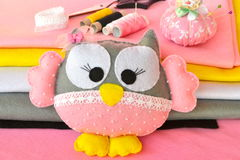 Funny felt owl toy, thread, pincushion with pins, felt sheets. Sewing concept Royalty Free Stock Photo