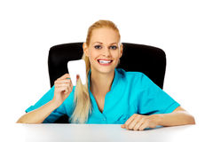 Funny female dentist sitting behing the desk and holding oversized tooth model Royalty Free Stock Images
