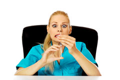 Funny female doctor or nurse sitting behind the desk and holding syringe.  Royalty Free Stock Image