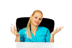 Funny female doctor or nurse sitting behind the desk and holding syringe.  Stock Photography