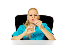 Funny female doctor or nurse sitting behind the desk and holding syringe.  Royalty Free Stock Photography