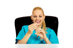 Funny female doctor or nurse sitting behind the desk and holding syringe.  Stock Image