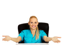 Funny female doctor or nurse sitting behind the desk with open arms.  Royalty Free Stock Images